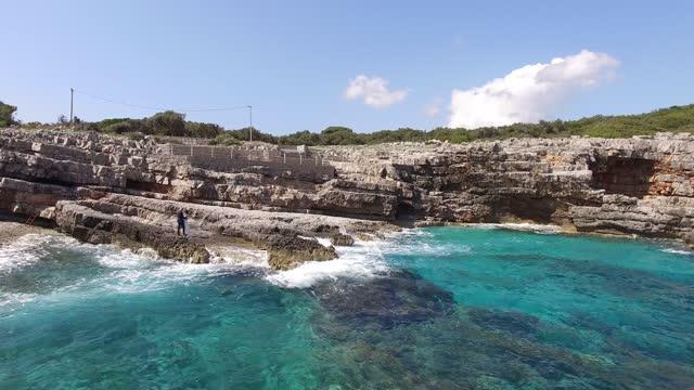 vídeos de stock, filmes e b-roll de noiva e noivo abraçando-se na costa rochosa em lustica - multicóptero