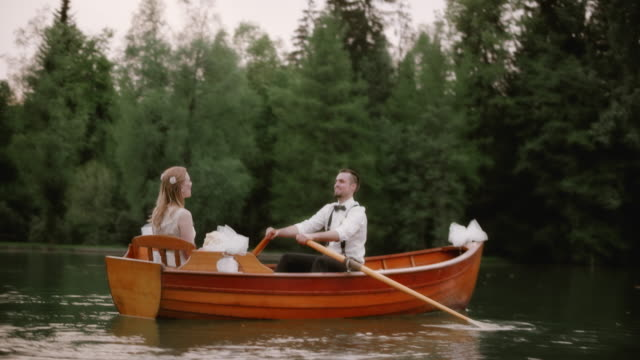 SLO MO Bride and groom in a rowing boat on a lake video