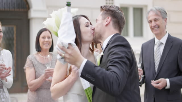 SLO MO Bride and groom kissing after opening a bottle of sparkling wine Slow motion medium handheld shot of the bride and groom kissing after he opens a bottle of sparkling wine outside the church after ceremony. newlywed stock videos & royalty-free footage