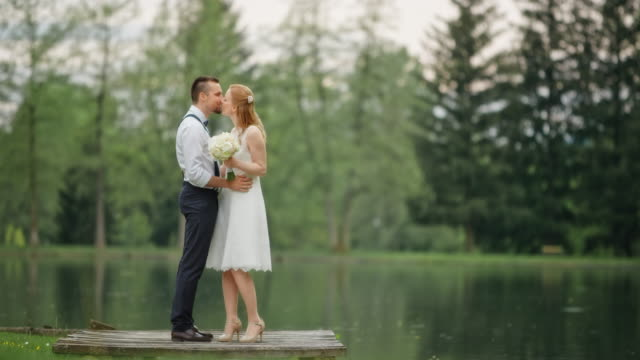 SLO MO Bride and groom kissing by the lake Slow motion wide locked down shot of the bride and groom kissing by the lake. heterosexual couple stock videos & royalty-free footage