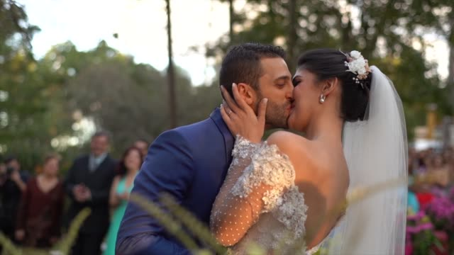 bride and groom kissing in the altar - matrimonio video stock e b–roll