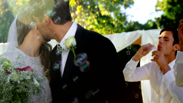 Bride and groom kissing while guest blowing bubbles 4K 4k video