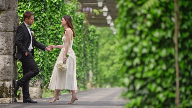 SLO MO Bride and groom meeting in an ivy covered passageway video