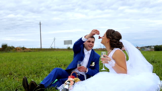 Bride and groom on a green meadow in summer day