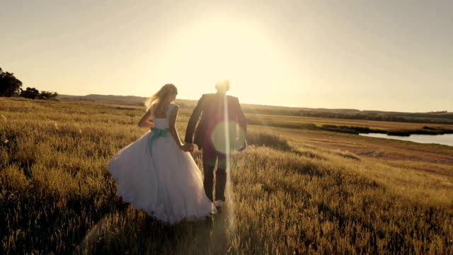 bride and groom running through the field to meet the sun at sunset bride and groom running through the field to meet the sun at sunset, slow motion newlywed stock videos & royalty-free footage