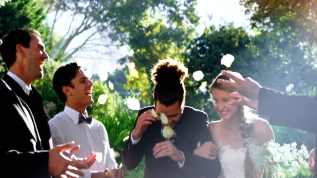 bride and groom walking down while guests toss petals 4k 4k - bouquet video stock e b–roll