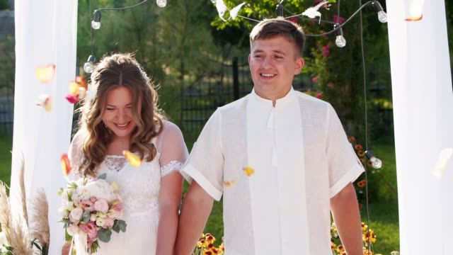bride and groom walking from wedding ceremony arch outdoors. guests throwing rose petals above newlyweds greeting new family in slow motion. couple on summer wedding - young couple wedding friends video stock e b–roll