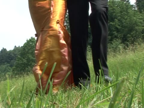 Bride And Groom Walking Bride and groom walking on a meadow. Close up view on the legs. mid adult men stock videos & royalty-free footage