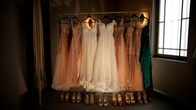 bride bridesmaids klänningar, brudklänning och skor hänger framför fönstret före ceremonin - aftonklänning bildbanksvideor och videomaterial från bakom kulisserna