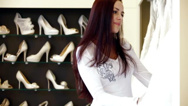 bride buying a wedding gown in bridal store - aftonklänning bildbanksvideor och videomaterial från bakom kulisserna