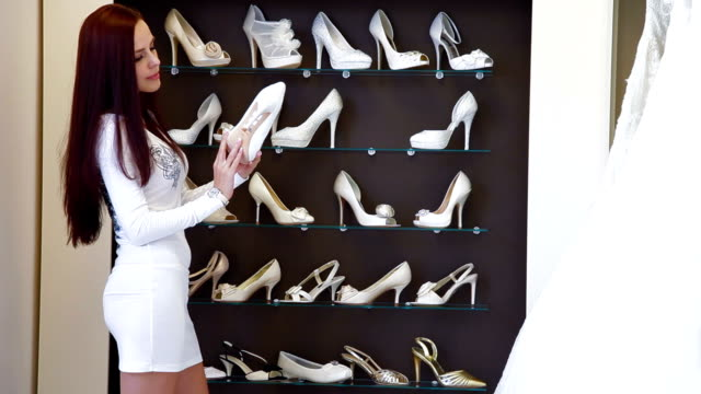 bride choosing wedding shoes in bridal shop - wedding fashion stock videos and b-roll footage
