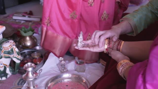 bride & brudgummen hålla en religiös hinduisk staty under deras bröllops ceremonin. - india statue bildbanksvideor och videomaterial från bakom kulisserna
