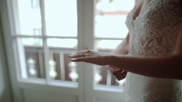 Bride hands with wedding ring and bracelet on, near the window