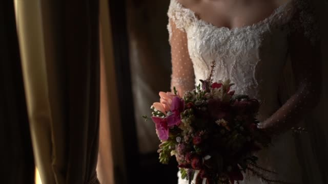 Bride holding bouquet and looking through the window before wedding ceremony