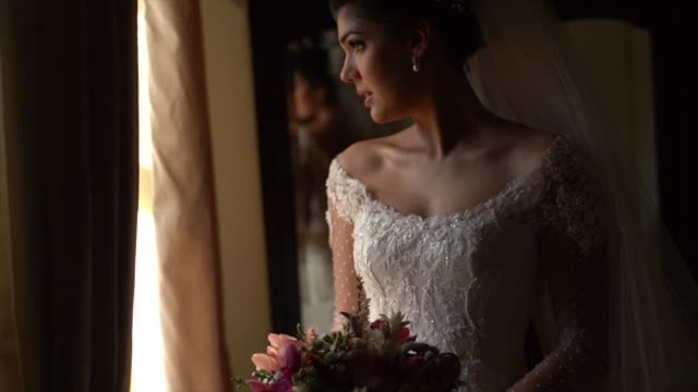 Bride holding bouquet and looking through the window before wedding ceremony Bride holding bouquet and looking through the window before wedding ceremony anticipation stock videos & royalty-free footage
