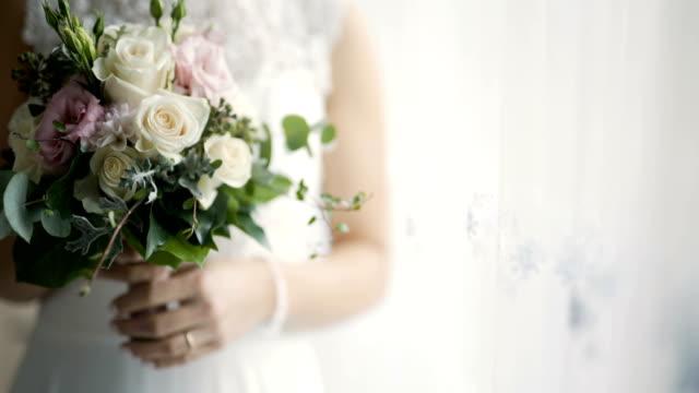 vídeos de stock, filmes e b-roll de noiva segurando flores nas mãos - casamento