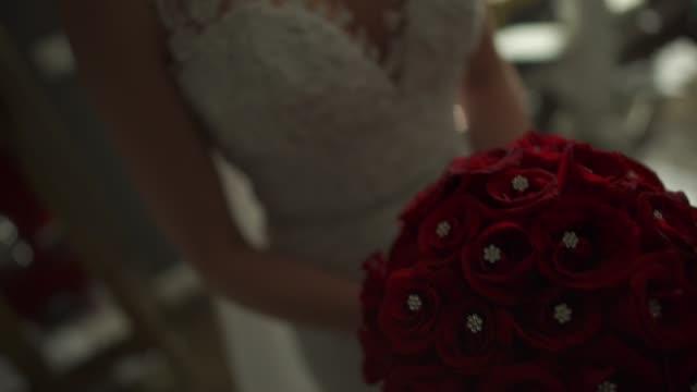 vídeos de stock, filmes e b-roll de noiva segurando seu buquê de flores vermelhas - moda de casamento