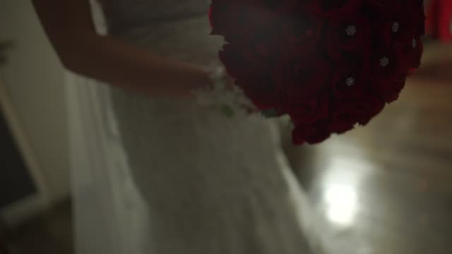 Bride holding her bouquet of red flowers