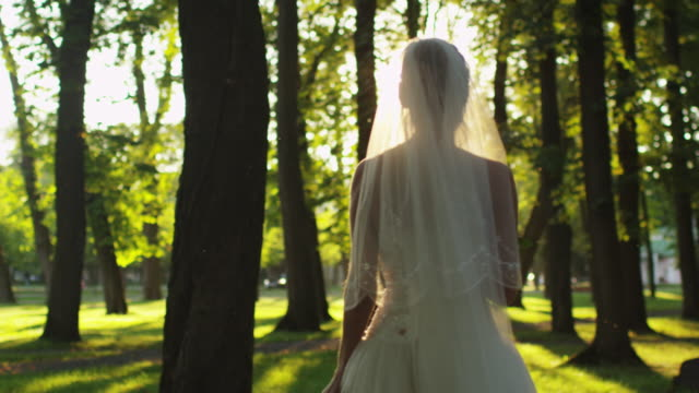 Bride is throwing a flower bouquet at wedding in a sunny park. video
