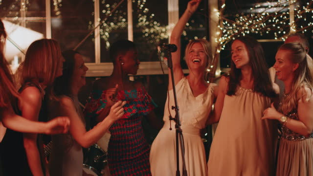Bride singing with friends at wedding reception