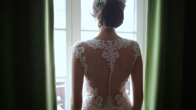 Bride standing in hotel room and looking through the window