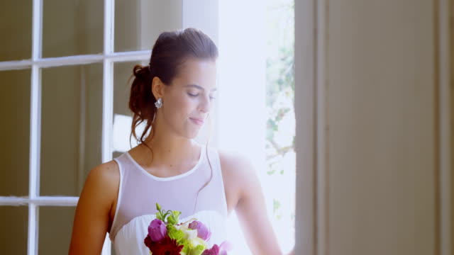 Bride standing near the window with a bouquet 4K 4k video