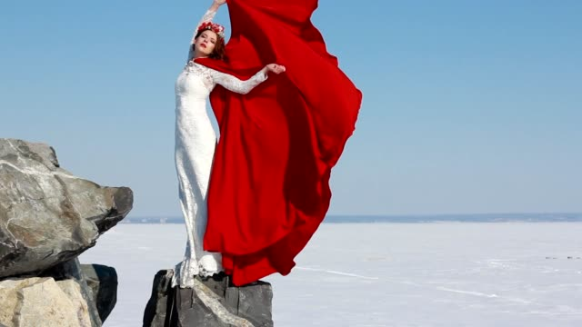 Bride stands on cliff with a flowing red raincoat on the wind against the blue sky and winter background. video
