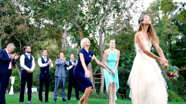 bride throwing wedding bouquet to wedding guest 4k 4k - bouquet video stock e b–roll