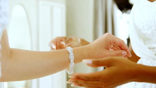 bride wearing white diamond bracelet and bridesmaid holding her hand 4k 4k - браслет стоковые видео и кадры b-roll