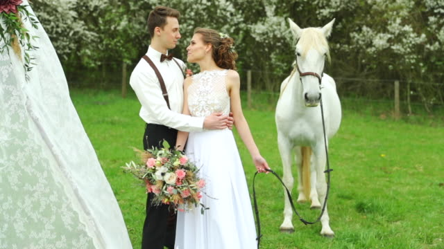 Bride with groom holding white horse to side of them and wedding teepee making background in nature. Bride with groom holding white horse to side of them and wedding teepee making background in nature. newlywed stock videos & royalty-free footage