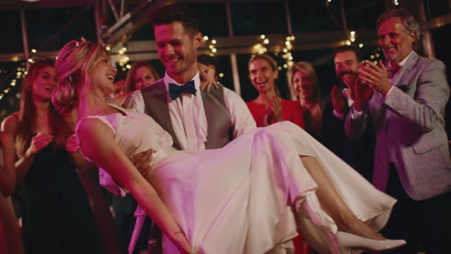 bridegroom carrying bride while dancing in wedding - young couple wedding friends video stock e b–roll