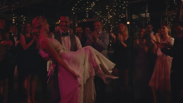 bridegroom carrying bride while dancing on floor - young couple wedding friends video stock e b–roll