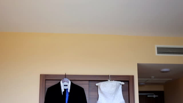Bridegroom dress and bridal gown hanging