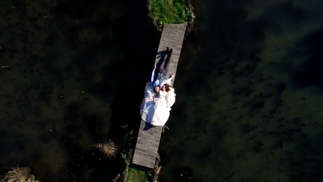 brides are lying on a small bridge in the park. aerial view on top. filming a dron, the camera flies away from the brides - video di matrimonio video stock e b–roll