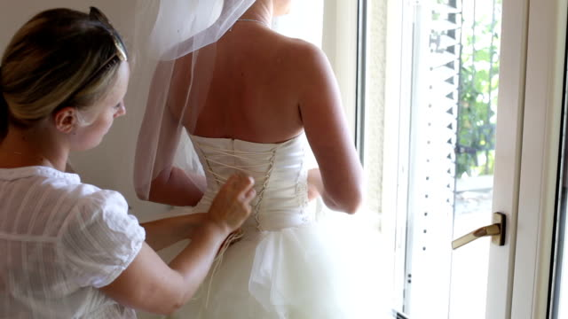 bridesmaid helps the bride to wear a dress - wedding fashion stock videos and b-roll footage