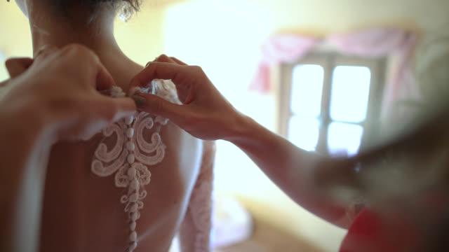 bridesmaid preparing bride for the wedding. bridesmaid buttoning wedding dress - tradycja filmów i materiałów b-roll