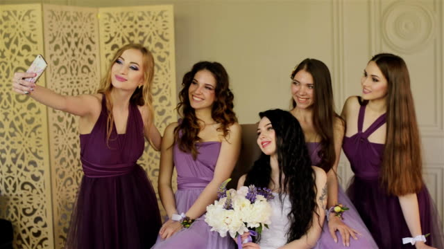 bridesmaids are photographed on a smartphone and laugh during the morning of the bride in a beautiful photo studio. beautiful girls in purple wedding dresses have fun in the studio. - young couple wedding friends video stock e b–roll