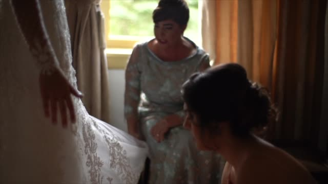 bridesmaids (mother and sister) helping bride getting dressed for the wedding ceremony - video di matrimonio video stock e b–roll