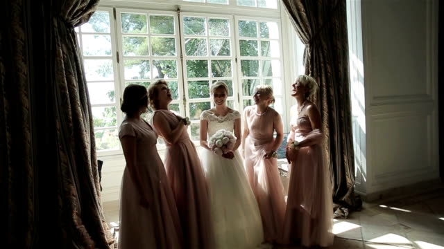 bridesmaids laughing happy near bride slow motion. beautiful girlfriends pose surrounding bride amusing and talking in sun light room. bachelorette party emotional. elegant wedding dress fashion style - wedding fashion stock videos and b-roll footage