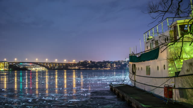 Bridge and frozen bay at night 4K Time Lapse. Quay and boat, lights reflected on the ice video