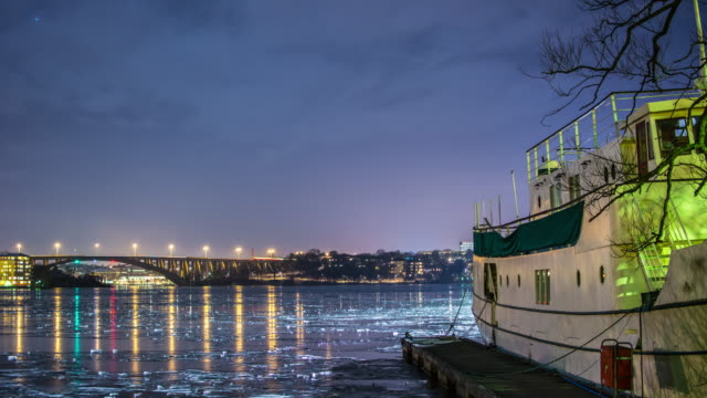 Bridge and frozen bay at night 4K Time Lapse Tilt. Quay and boat, lights reflected on the ice video