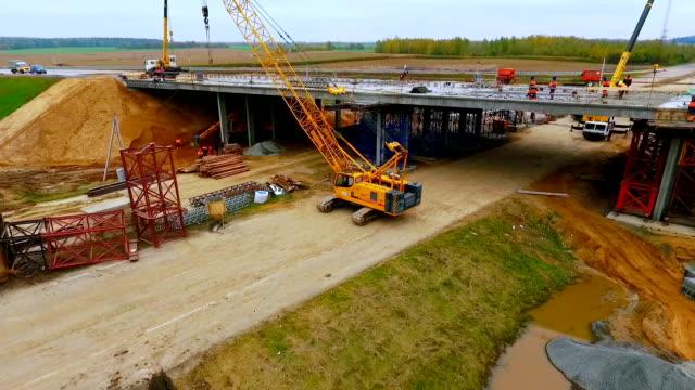 vidéos et rushes de construction d'un pont. vue du ciel de crawler crane réparation pont sur route - chantier