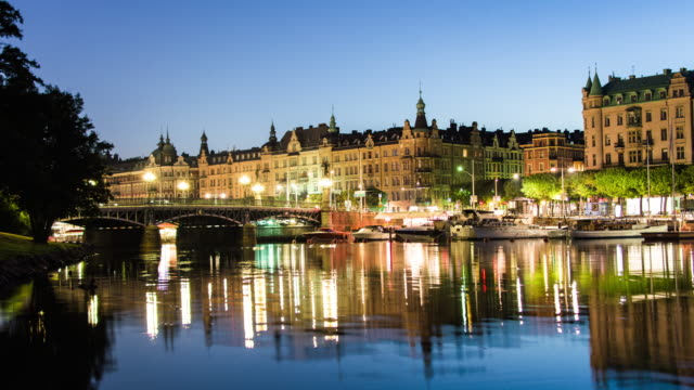 Bridge in central Stockholm at night 4K Time Lapse Tilt. City river, buildings, reflections in the water video