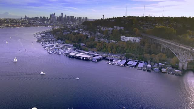 Bridge in Pacific Northwest Aurora Bridge connecting Fremont to Queen Anne in Seattle. Boats float on Lake Union with the iconic backdrop of the Seattle city skyline with the Space Needle and Mount Rainier. seattle stock videos & royalty-free footage