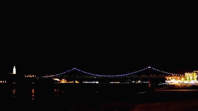 vídeos de stock e filmes b-roll de bridge of 25th april in lisbon at night. - ponte 25 de abril