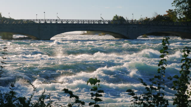 Bridge over the Niagara River to the waterfall. Vibrant river flowing underneath. A popular place among tourists video