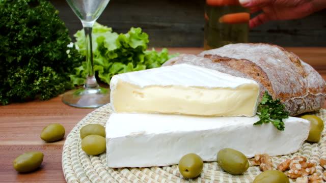 brie-käse, oliven und brot mit weißwein - brie stock-videos und b-roll-filmmaterial