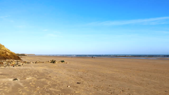 Bright Blue Sky, sandy lonely beach stretching to shore video