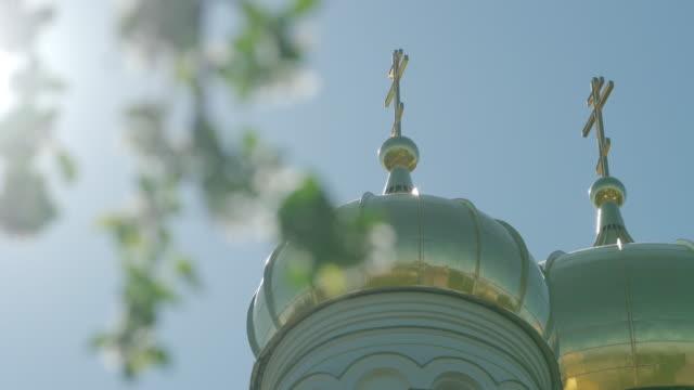 helle christliche kirche goldene kuppeln im sonnenlicht gegen blauen klaren himmel und sonne - religiöses symbol stock-videos und b-roll-filmmaterial
