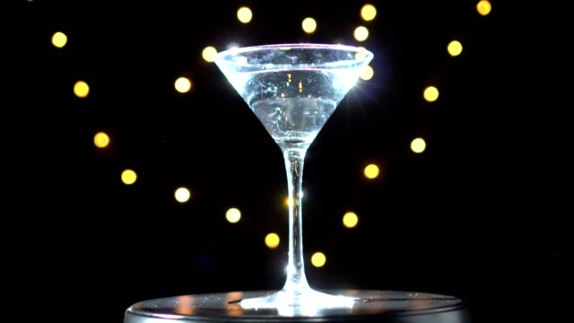 Bright cocktail in glass, spinning and change colours on dark background with blurred light. video